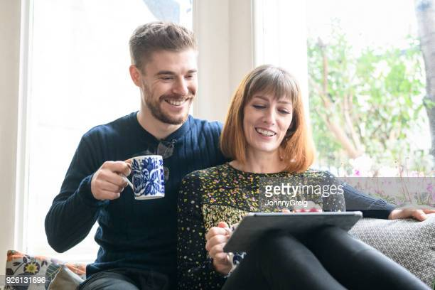 Mid adult couple by window using digital tablet and smiling