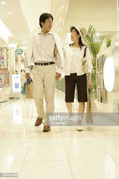Mid adult couple carrying shopping bags in a shopping mall