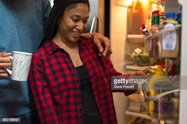 Mid adult couple choosing food from refrigerator in kitchen