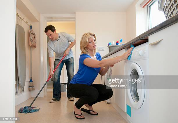 Mid adult couple cleaning kitchen in new home