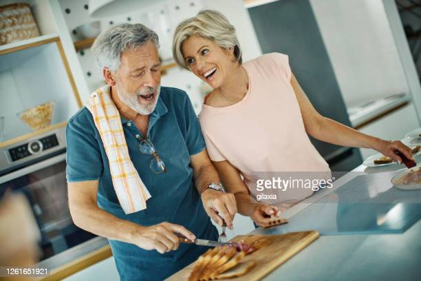 mid adult couple cooking lunch together. - brightly lit stock pictures, royalty-free photos & images