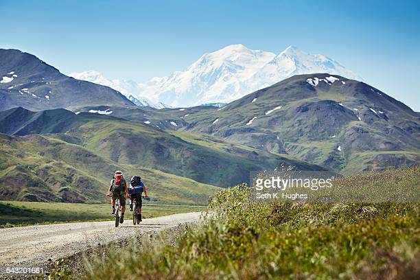 Mid adult couple cycling on rural road, Mount McKinley, Denali National Park, Alaska, USA