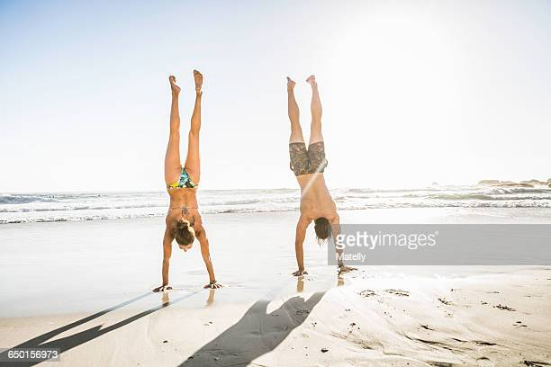 Mid adult couple doing handstands on beach, Cape Town, South Africa