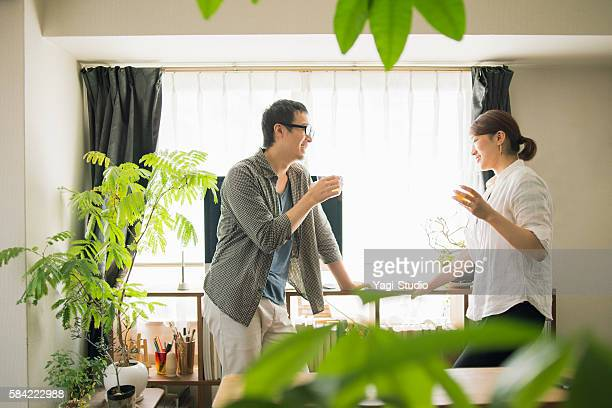 mid adult couple drinking beer at home - 夫婦 ストックフォトと画像
