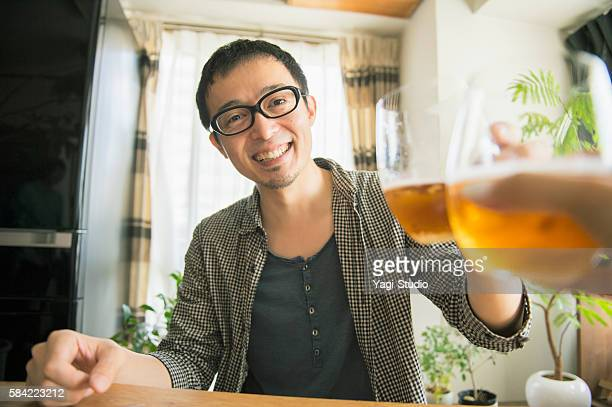 Mid adult couple drinking beer at home