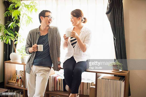 mid adult couple drinking coffee at home - 30代 ストックフォトと画像