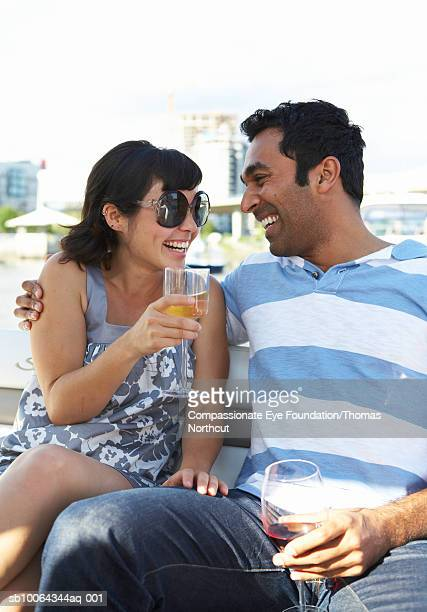 Mid adult couple drinking wine outdoors, laughing