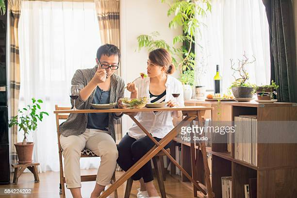 Mid adult couple eat lunch with wine