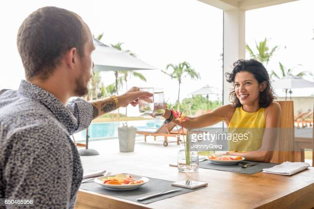 Mid adult couple enjoying lunch on vacation near pool