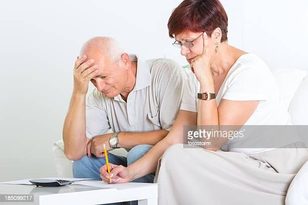 Paar mittleren Alters untersuchen Sie finanzielle Dokumente