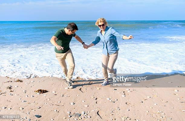 Mid adult couple fooling around on beach, Thurlestone, Devon, UK