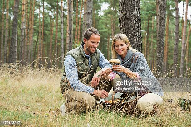 mid adult couple foraging for mushrooms in forest - foerageren stockfoto's en -beelden