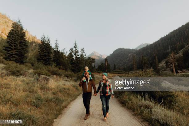 mid adult couple giving toddler daughter a shoulder carry on rural valley road, mineral king, california, usa - national park stock pictures, royalty-free photos & images