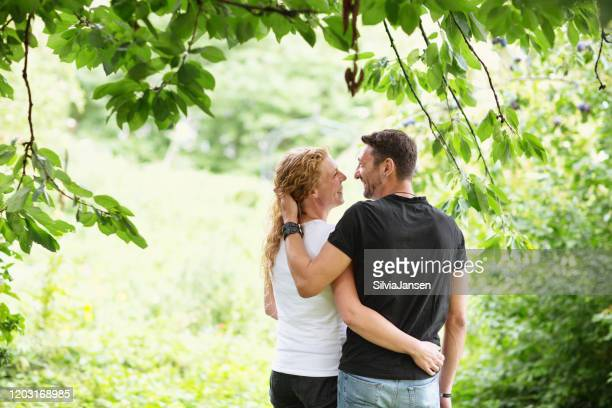 mid adult couple happy together outdoors in nature - black shirt stock pictures, royalty-free photos & images