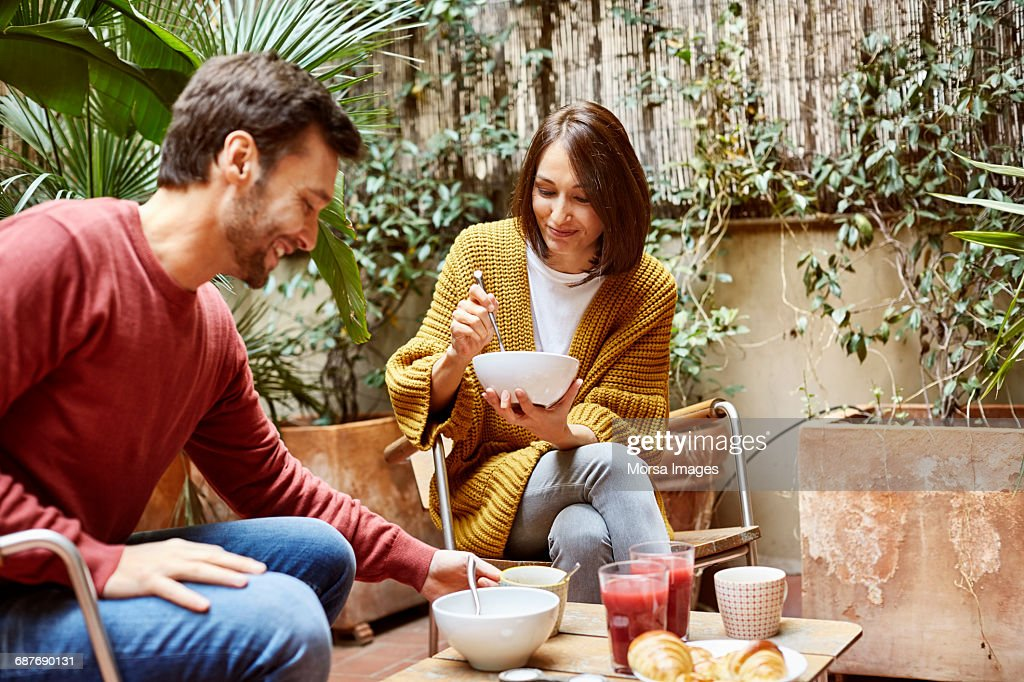 Mid adult couple having breakfast in yard : Stock Photo