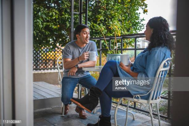 mid adult couple having coffee at porch - mid adult couple stock pictures, royalty-free photos & images