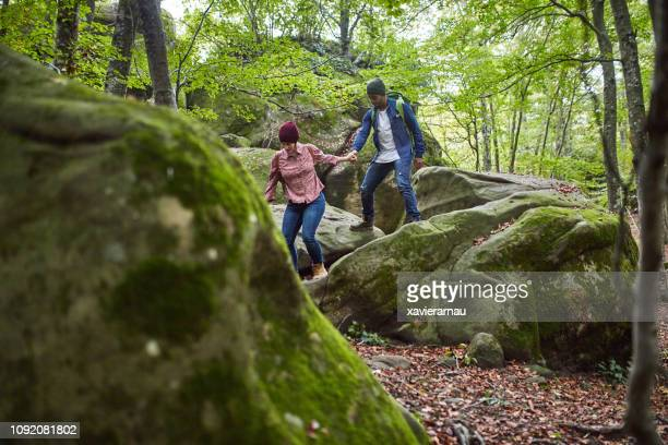 pareja adulto medio caminar sobre cantos rodados en bosque - turismo ecológico fotografías e imágenes de stock