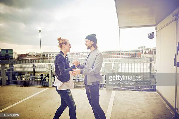 Mid adult couple holding hands and laughing on rooftop parking lot