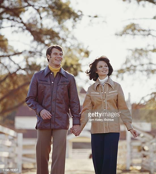 中年カップル手をつなぐとウォーキング、笑顔 - 1975年 ストックフォトと画像