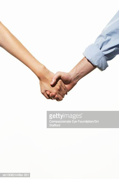 """mid adult couple holding hands, mid section - """"compassionate eye"""" stock pictures, royalty-free photos & images"""