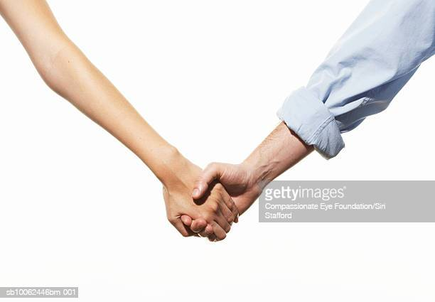 Mid adult couple holding hands, mid section
