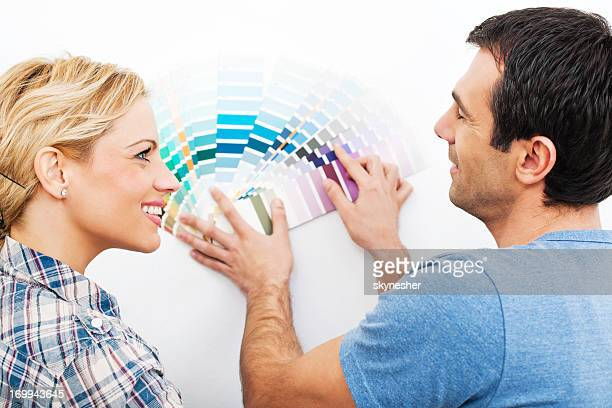 Mid adult couple holding paint swatches.
