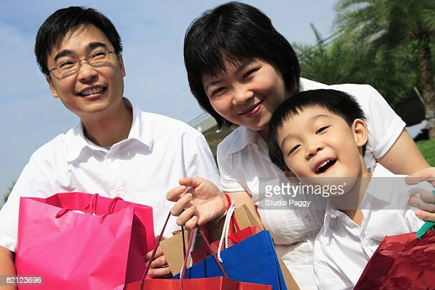 Mid adult couple holding shopping bags with their son and smiling