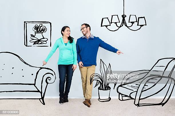 Mid adult couple imagine life in their new home