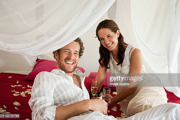 mid adult couple in hotel room with champagne - mosquito net stock photos and pictures