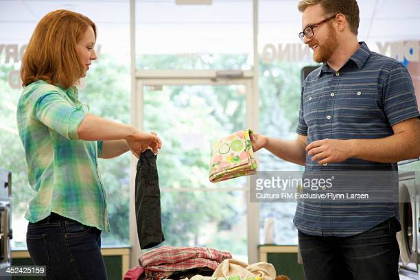Mid adult couple in launderette, folding laundry