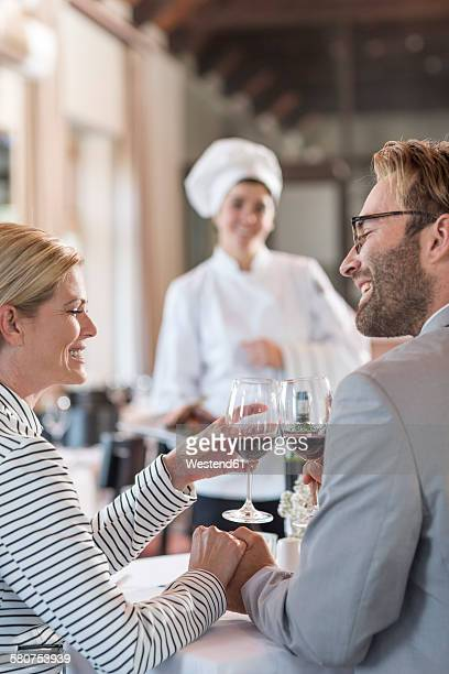 Mid adult couple in restaurant toasting with redwine