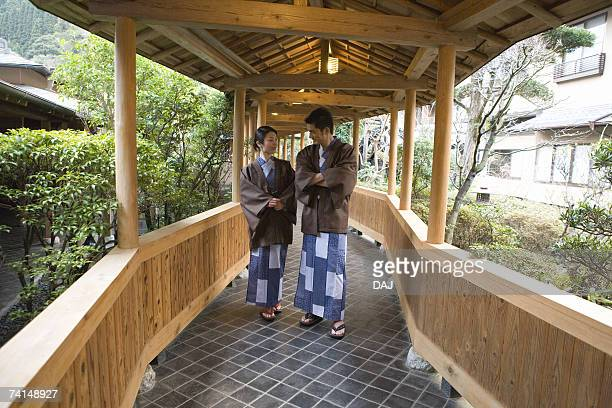 Mid Adult Couple in Yukata, Walking on the Outside Corridor, Front View