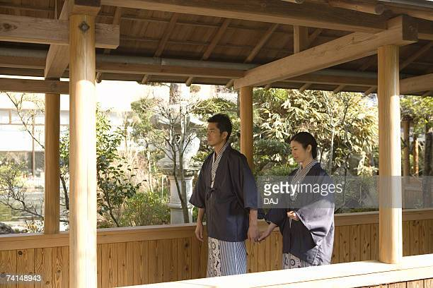 mid adult couple in yukata, walking on the outside corridor, holding hands, side view - 日本建築 ストックフォトと画像