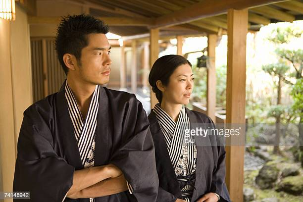 Mid Adult Couple in Yukata, Walking on the Outside Corridor, Looking at the Japanese Garden, Front View