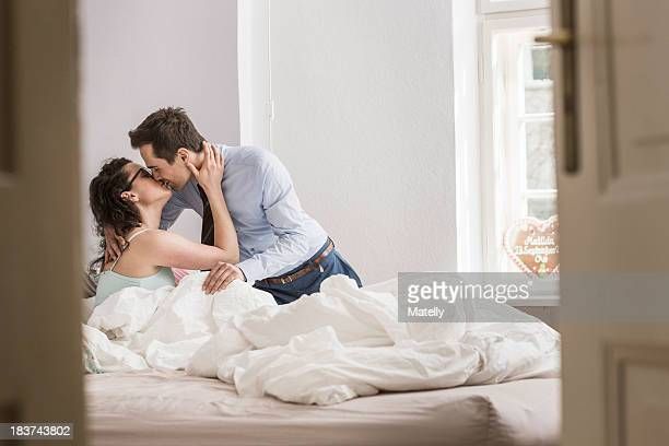 mid adult couple kissing on bed - kissing on the mouth stock photos and pictures