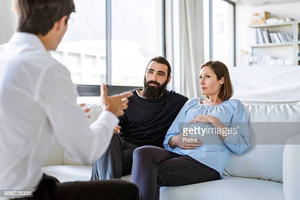 Mid adult couple listening to advisor at home