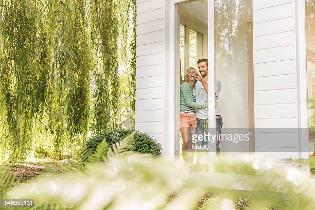 Mid adult couple looking and pointing through house window