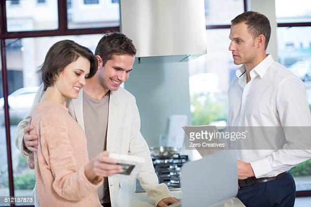Mid adult couple looking at computer in kitchen showroom
