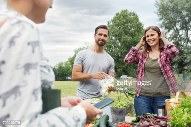 Mid adult couple looking at female customer at vegetable garden