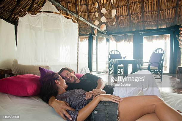 Mid adult couple lying on bed in beach hut