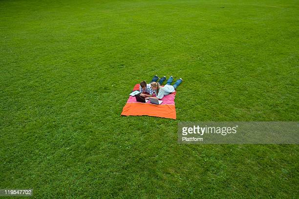 mid adult couple lying on blanket with laptops - lying on front stock pictures, royalty-free photos & images