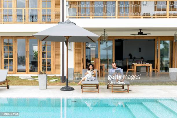 mid adult couple lying on sun loungers on poolside - sun lounger stock pictures, royalty-free photos & images