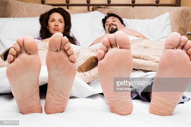 mid adult couple lying on the bed - male feet soles stock photos and pictures