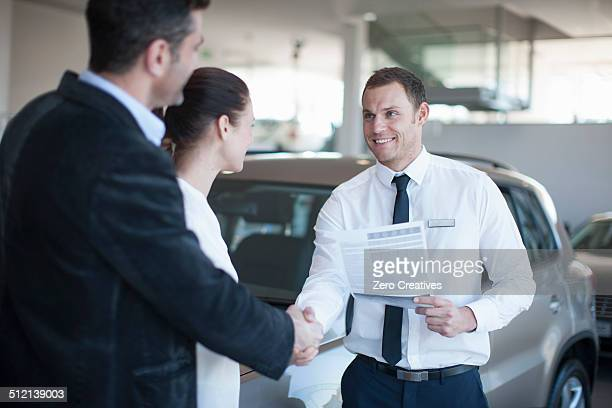 Mid adult couple making deal with salesman in car dealership
