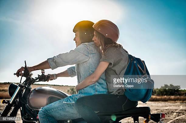 Mid adult couple motorcycling on arid plain, Cagliari, Sardinia, Italy
