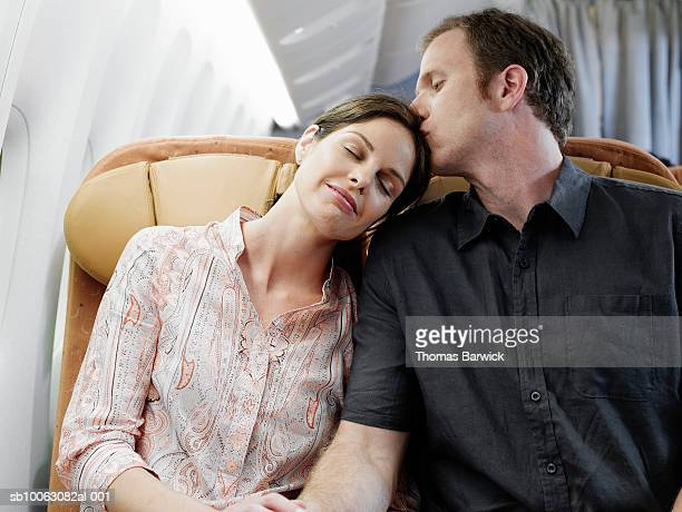 Mid adult couple on airplane, man kissing wife on top of head