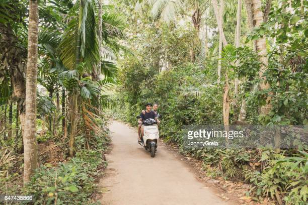 Mid adult couple on moped in forest