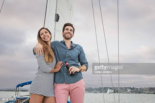 Mid adult couple on sailing boat, man with arm round woman