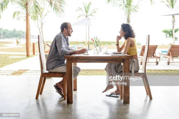 Mid adult couple on vacation enjoying lunch near patio