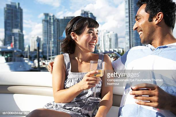 """mid adult couple on yacht drinking wine, cityscape in background - """"compassionate eye"""" stock pictures, royalty-free photos & images"""